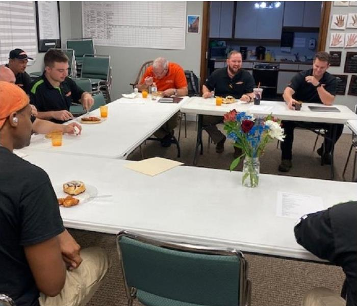 SERVPRO team members sitting around table eating breakfast