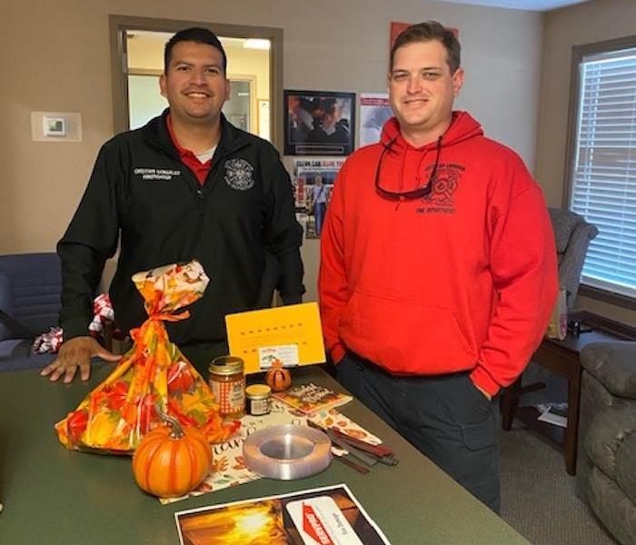 2 male firefighters standing at a counter with food on it