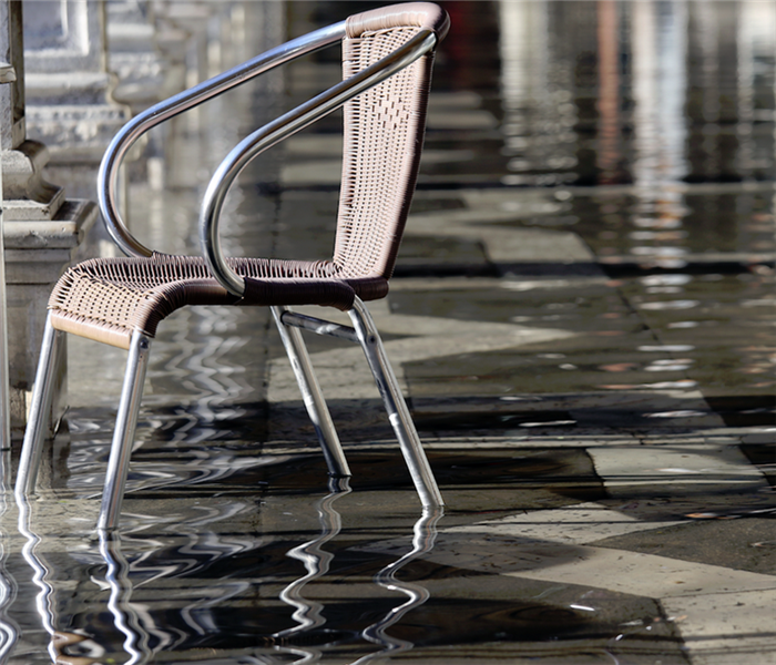 a flooded room over tile floor with chairs floating