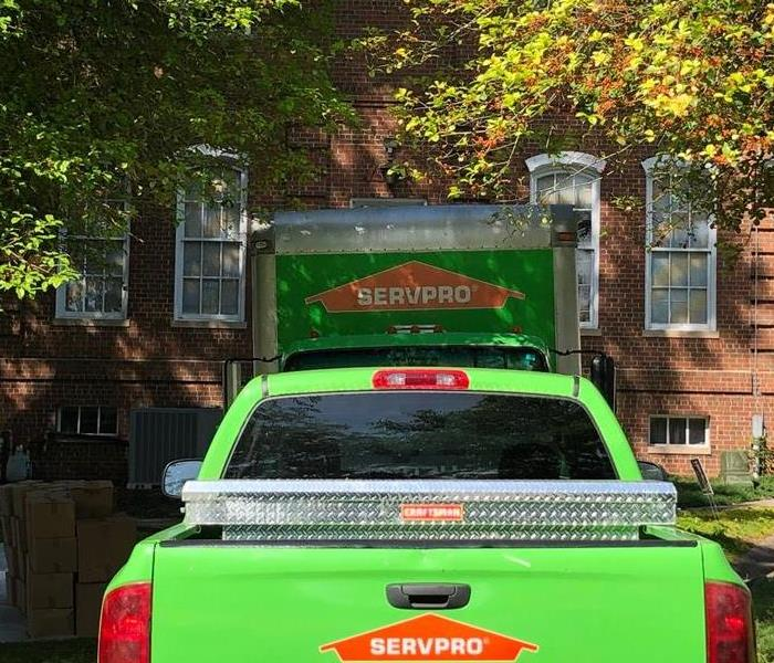 Two SERVPRO vehicles in a homeowners driveway.