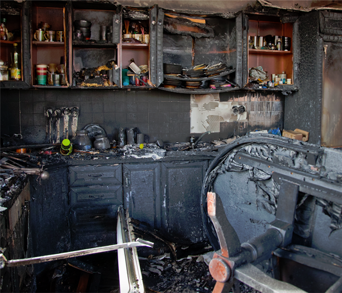 a fire damaged kitchen with debris everywhere